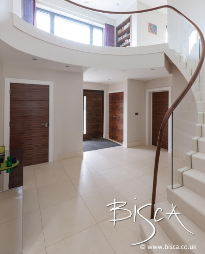 Stone staircase by Bisca with glass balustrade and hand polished timber handrail