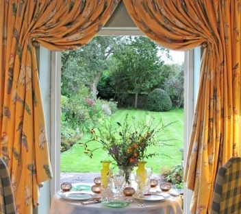 A classic table setting with parrot curtains as a surround