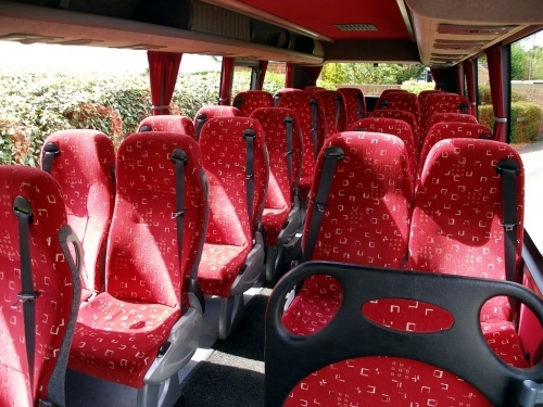 This photo shows the interior from one of our 26 seater vehicles with 3 point belts, reclining seats and air-con.